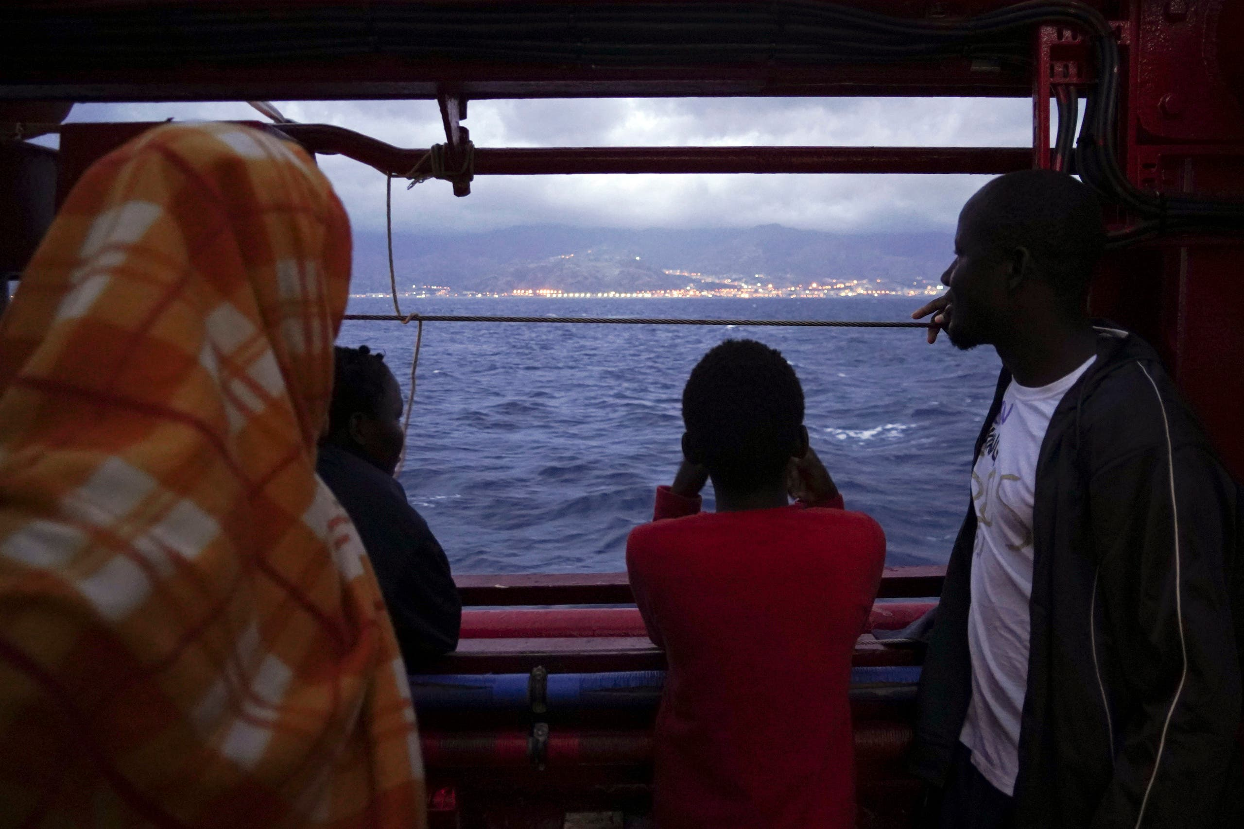 Migrants look at the Italian shoreline from aboard the Ocean Viking as it approaches the Sicilian port of Messina, southern Italy, on September 24, 2019. (AP)