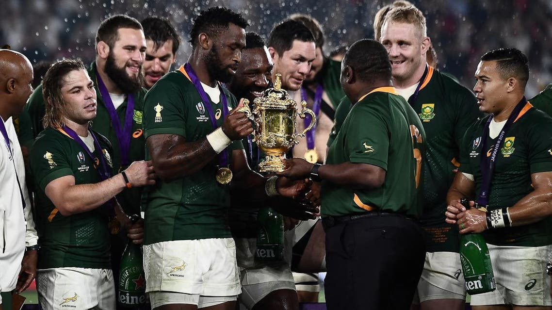 South Africa's President Cyril Ramaphosa (center R) and South Africa's flanker Siya Kolisi (center L) hold the Webb Ellis Cup as they celebrate winning the Japan 2019 Rugby World Cup final match between England and South Africa on November 2, 2019. (AFP)