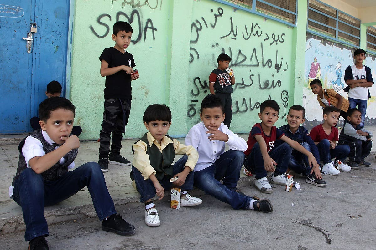 Palestinian refugee pupils wait outside a United Nations Relief and Works Agency's school, in the Baqa'a Palestinian refugee camp, near Amman, on September 2, 2018. (AFP)