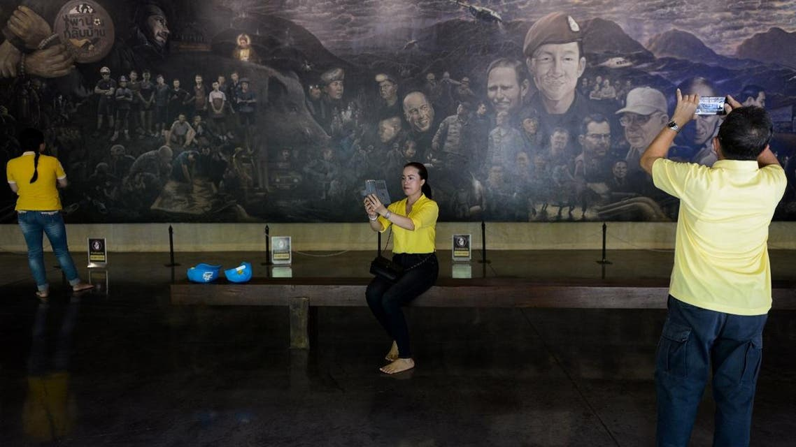 """Visitors take pictures at the Tham Luang cave center, which documents the rescue of the """"Wild Boars"""" football team from the cave a year ago, in the Mae Sai district of Chiang Rai province in Thailand. (File photo: AFP)"""