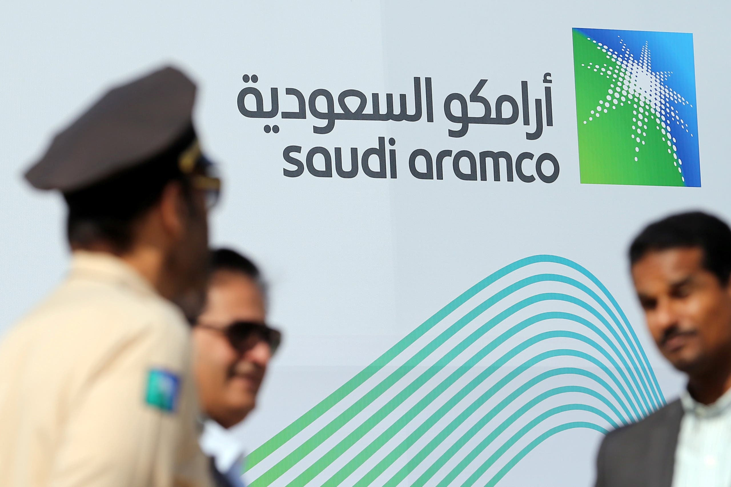 The logo of Aramco is seen as security personnel stand before the start of a press conference by Aramco at the Plaza Conference Center in Dhahran, Saudi Arabia November 3, 2019. (Reuters)