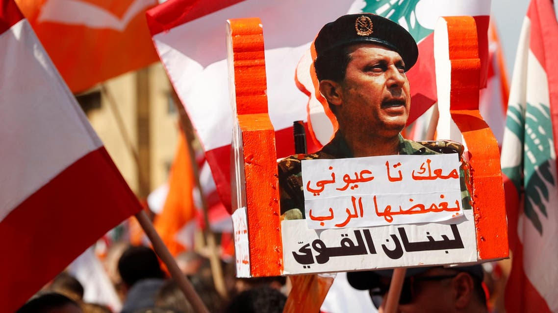A supporter of Lebanon's President Michel Aoun holds his pictures during a rally in Baabda near Beirut (reuters)