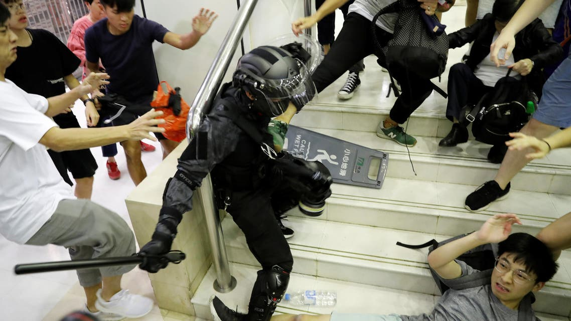 People scuffle with a riot police officer at a shopping mall in Tai Po in Hong Kong (reuters)