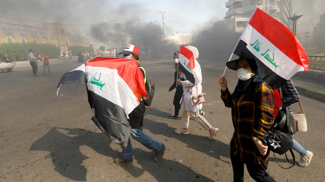 Iraqi demonstrators carry Iraqi flags as they walk at a cloud of smoke during ongoing anti-government protests, in Baghdad, Iraq November 3, 2019. REUTERS