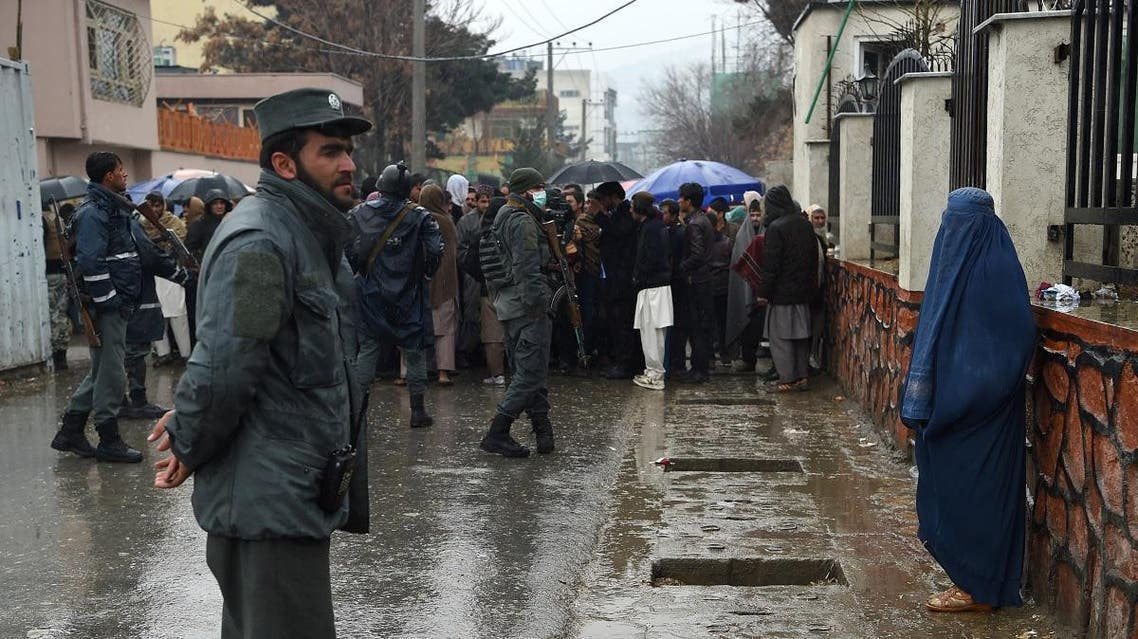 In this photo taken on March 11, 2019 Afghan policemen stand guard as people with visa issues queue up outside the Pakistan embassy in Kabul. (AFP)