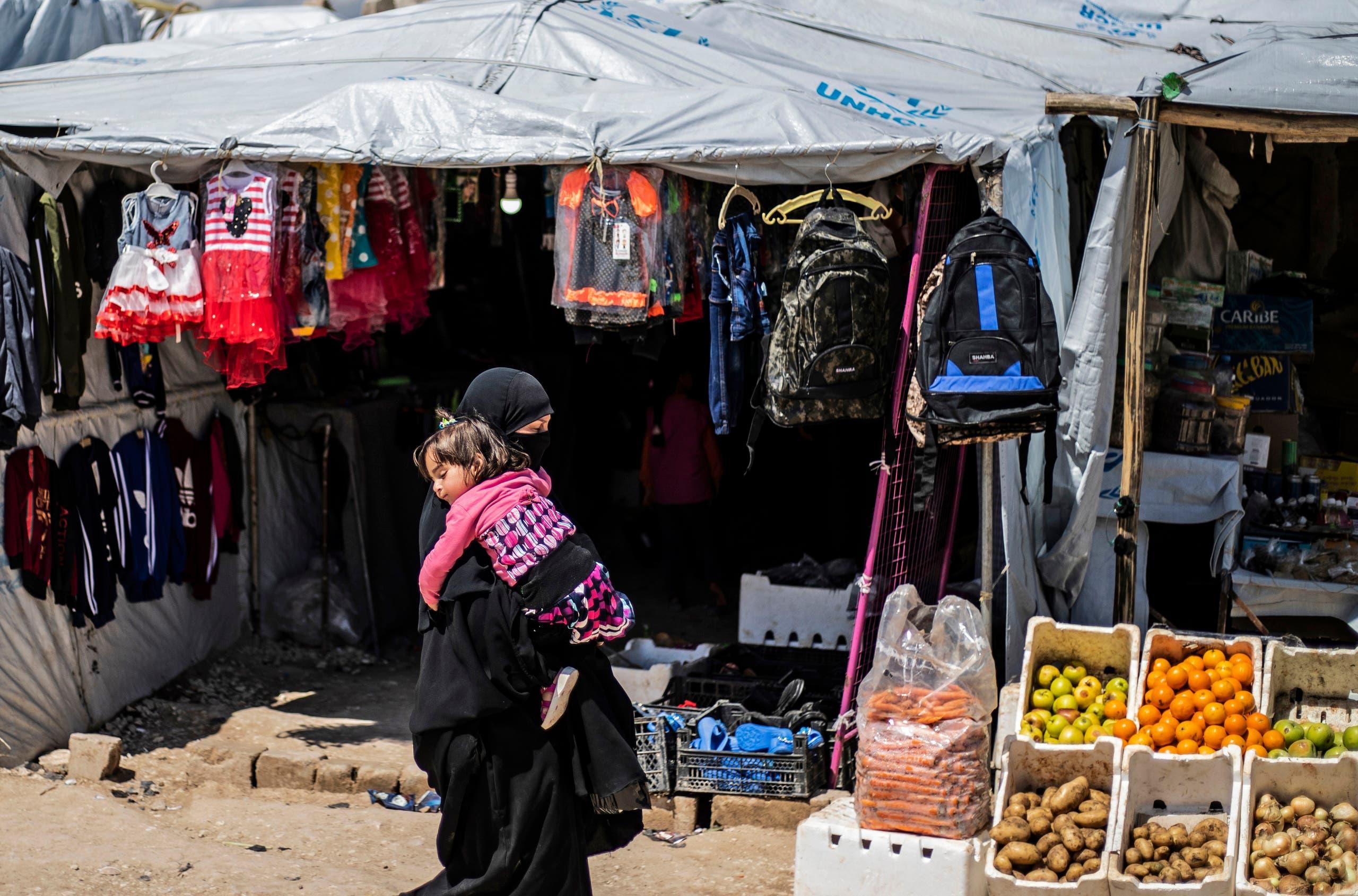 امرأة تحمل طفلة في مخيم الهول