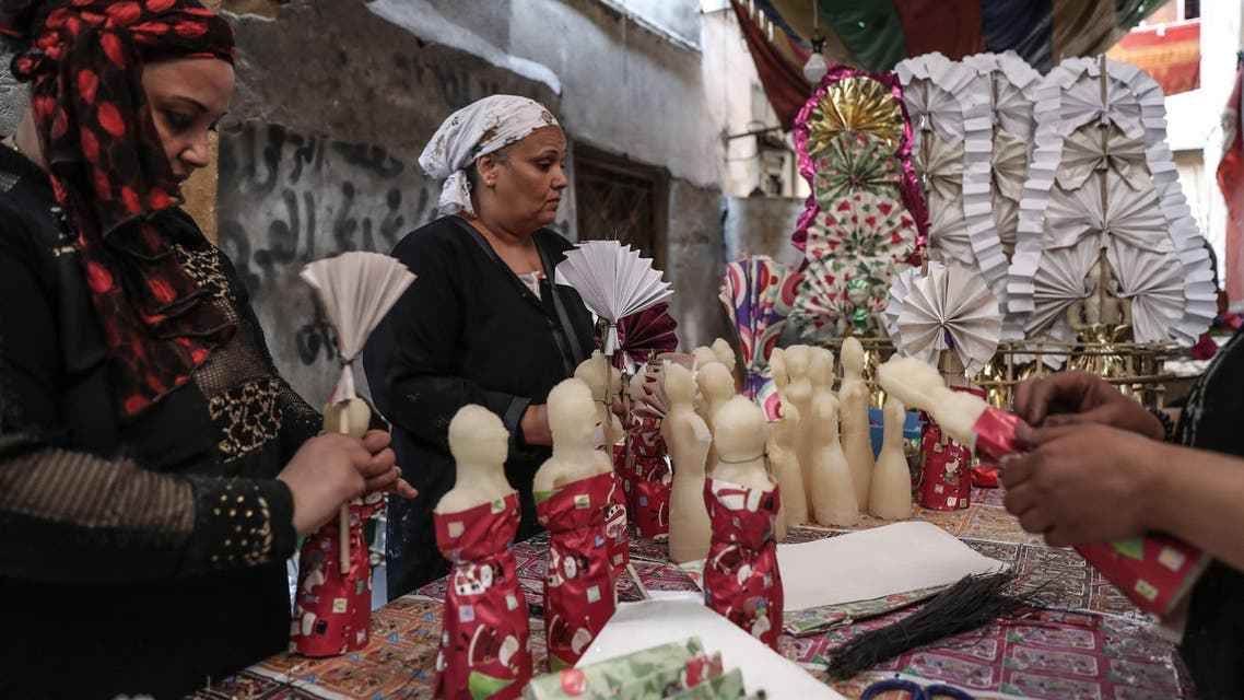 """Egyptian women decorate traditional sugar statuettes in the capital Cairo on November 2, 2019, ahead of celebrations of the Muslim Prophet Mohammed's birthday, known as """"Al Mawlid Al Nabawi"""". (AFP)"""