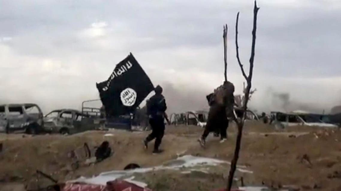 This frame grab from video posted online Monday, March 18, 2019, shows ISIS fighters carrying the group's flag inside Baghouz, Syria. (File photo: AP)