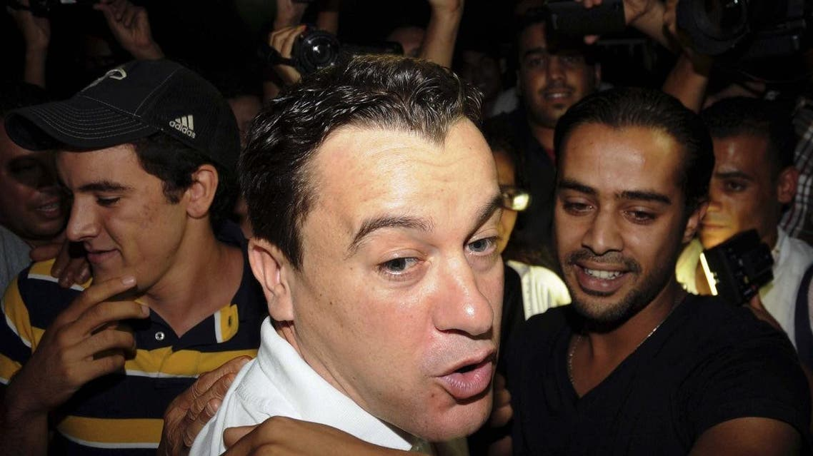 In this photo taken on Wednesday night, Sept. 11, 2013, Sami El Fehri, foreground, the head of a private Tunisian TV channel, reacts with the media, after being released after a year in prison, near Tunis. (AP)