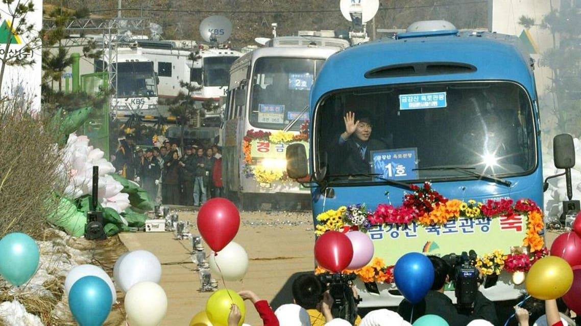 Buses carrying some 400 civilian travellers cross the heavily armed border separating the two Koreas in 2003 for a pilot road trip to the North's Diamond Mountain resort. (AFP)