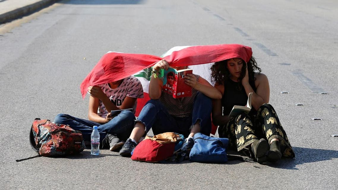 Demonstrators sit on the ground and read along a blocked road in Beirut. (Reuters)