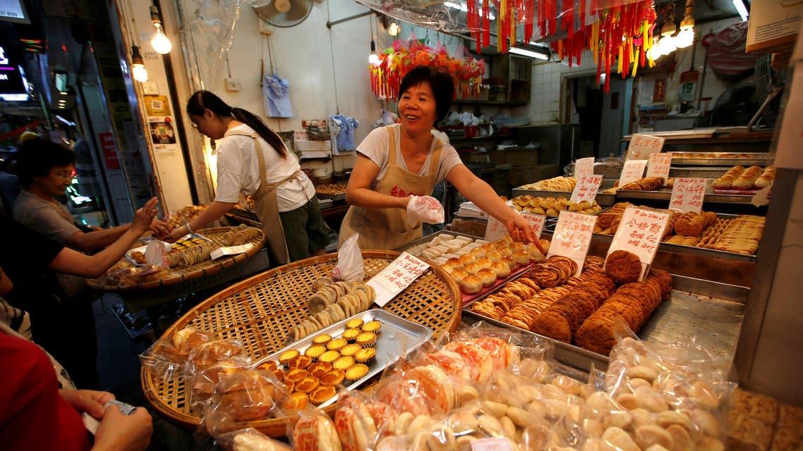china- reuters Vendors serve their customers at a cake shop at a traditional market in Hong Kong, China