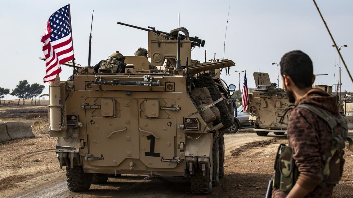 عنصر من قوات سوريا الديمقراطية إلى جانب آلية أميركية شمال سوريا(فرانس برس)