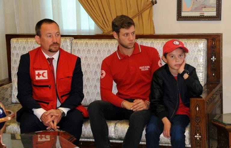 الطفل ألفين عندما التقى بمسؤولين من الصليب الأحمر في سوريا تمهيداً لإعادته إلى والده