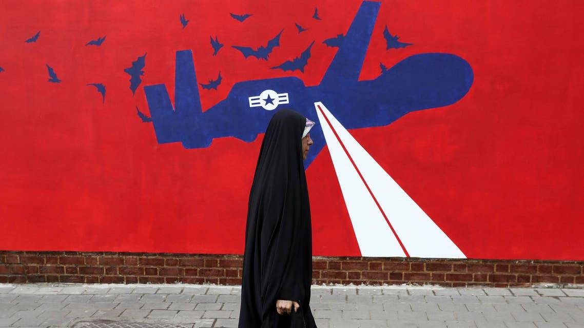 Iran drone mural woman walking past in Iran - AP