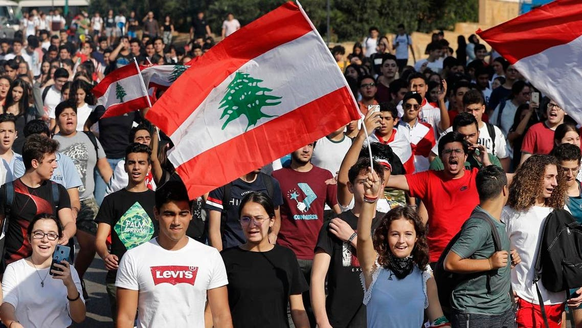 Student protesters wave their national flags and shout slogans, as they protest against the government in front of the education ministry in Beirut, Lebanon, on Nov. 8, 2019. (AP)