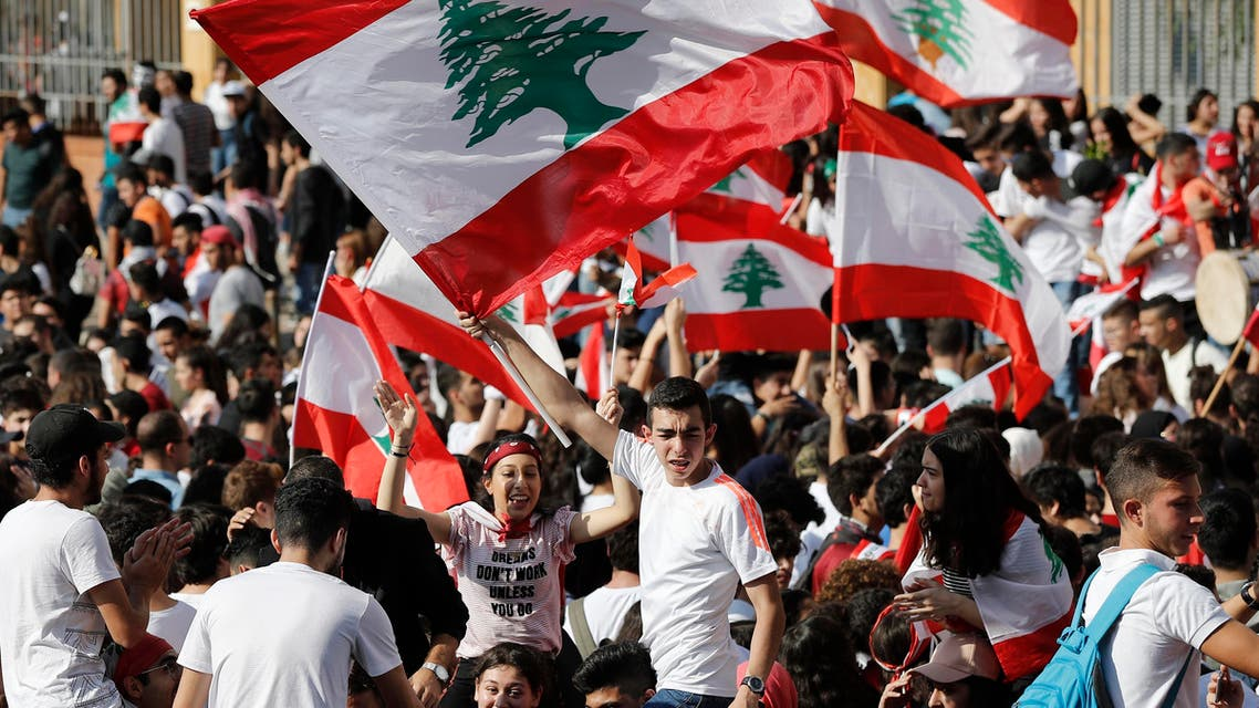 Student protesters wave their national flags as they protest against the government in front of the education ministry in Beirut, Lebanon, Friday, Nov. 8, 2019. (AP)
