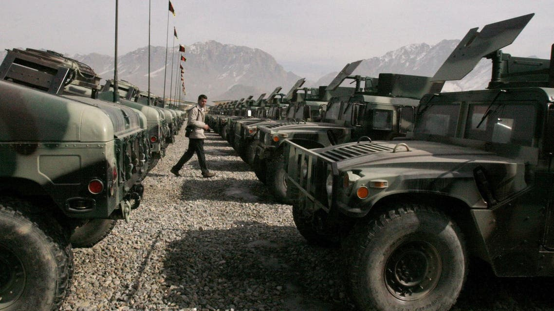 An Afghan photographer walks among the US Humvees during a ceremony of U.S. arms donation to Afghanistan's army on the out skirts of Kabul, Afghanistan on Thursday, Feb. 1, 2007. (AP)