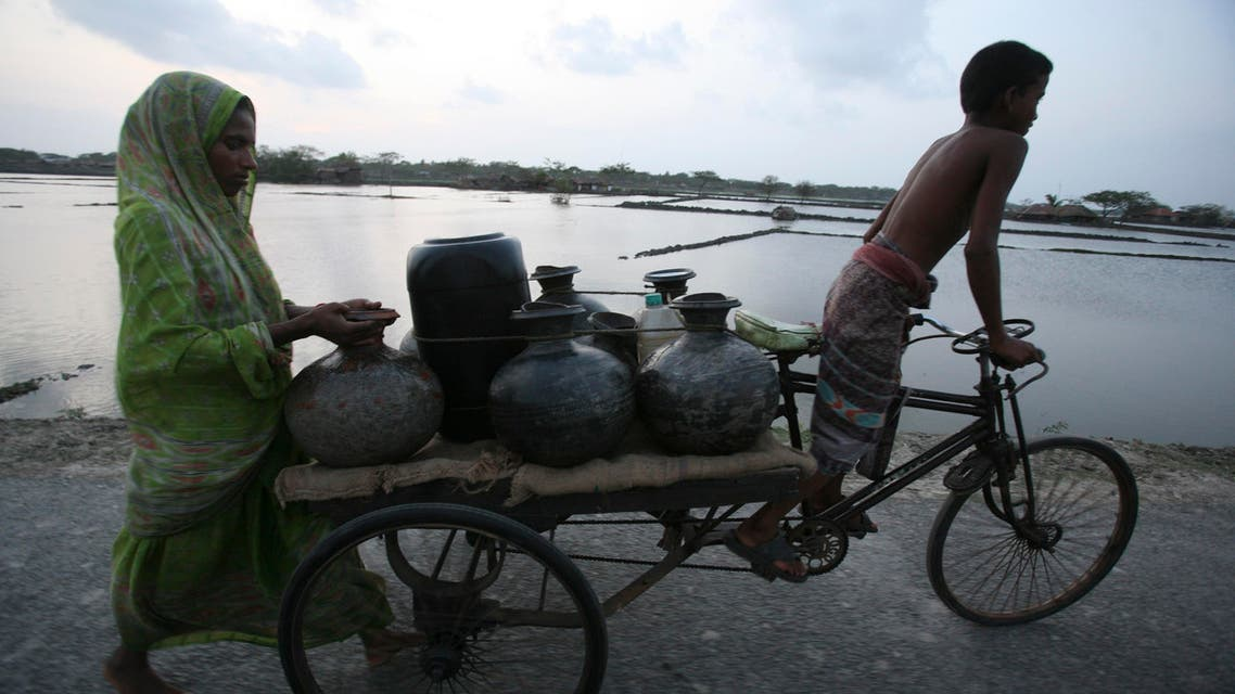 A mother and son transport drinking water on a cart in a cyclone affected area in Shatkhira, 176 kilometers (110 miles) south west of Dhaka, Bangladesh, Wednesday, May 27, 2009. (AP)