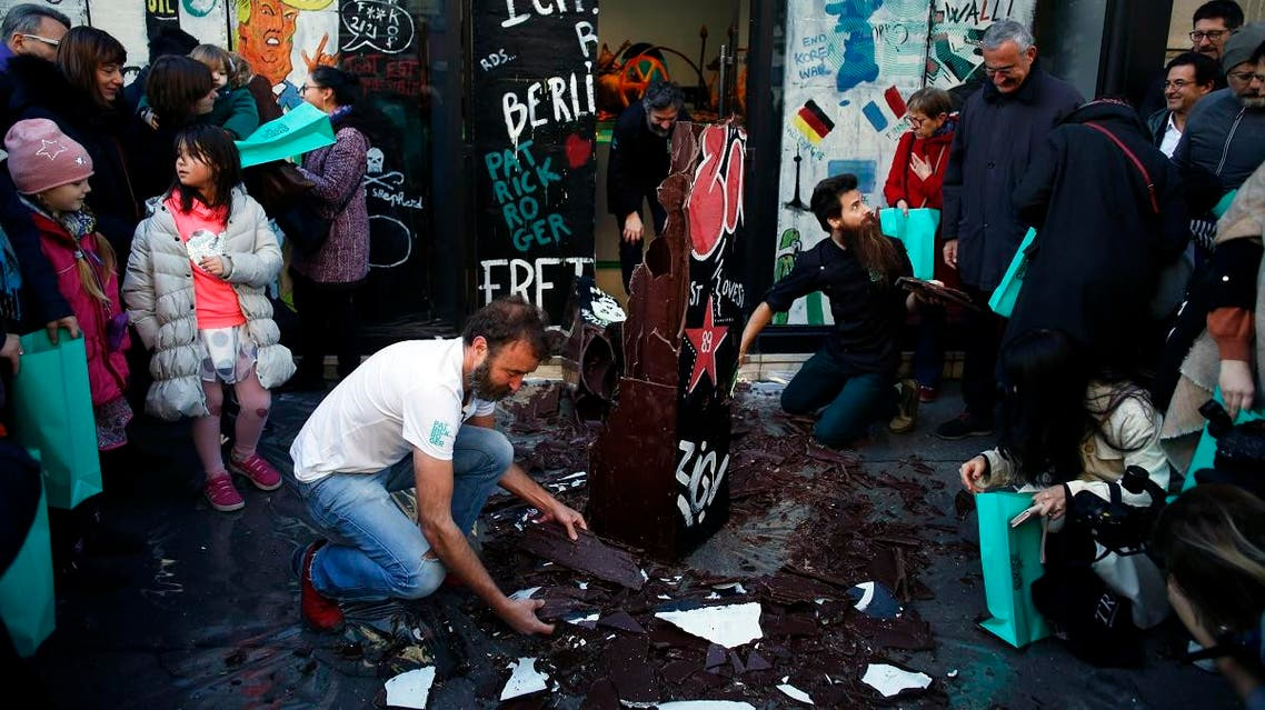 French chocolate maker Patrick Roger, center left, destroys a reproduction of the Berlin wall in chocolate, to mark the 30th anniversary of the fall of the Berlin Wall, in Paris, Saturday, Nov. 9, 2019. (AP)