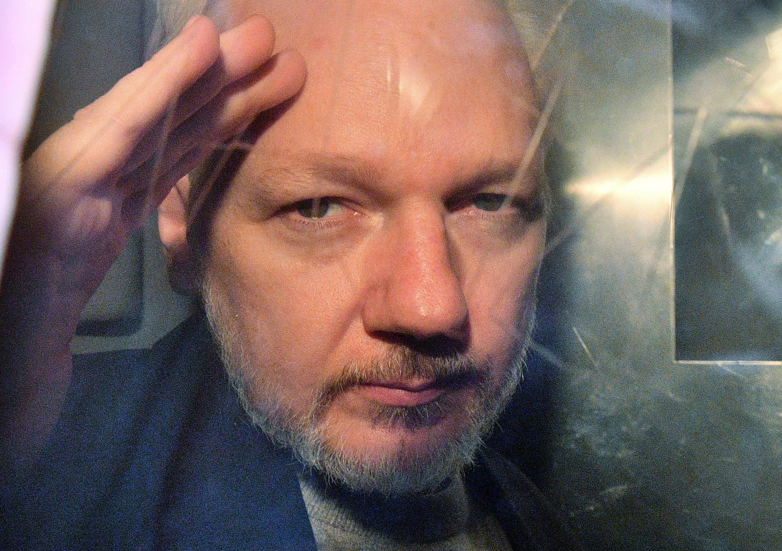 WikiLeaks founder Julian Assange gestures from the window of a prison van as he is driven out of Southwark Crown Court in London on May 1 2019. (Stock image)