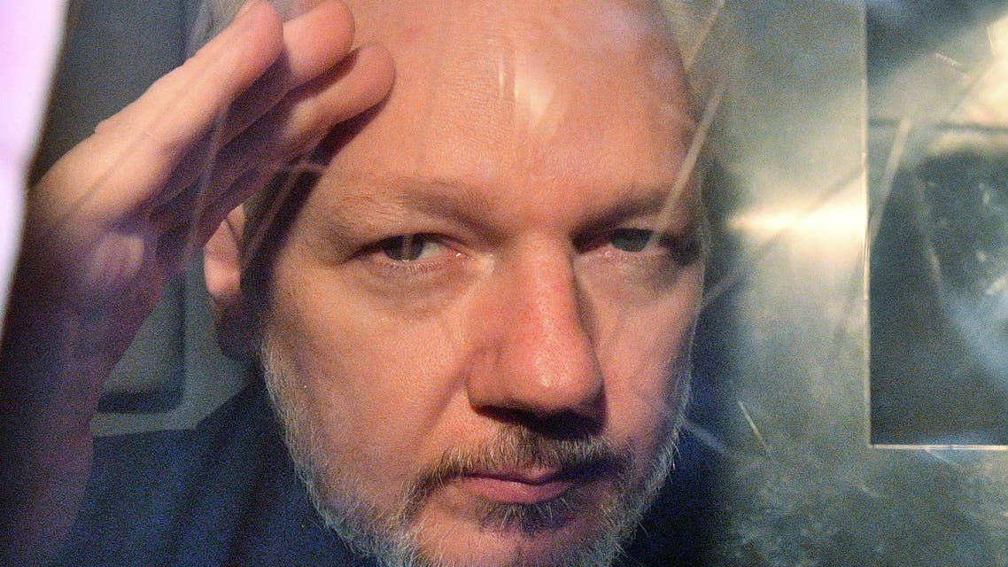 WikiLeaks founder Julian Assange gestures from the window of a prison van as he is driven out of Southwark Crown Court in London on May 1 2019