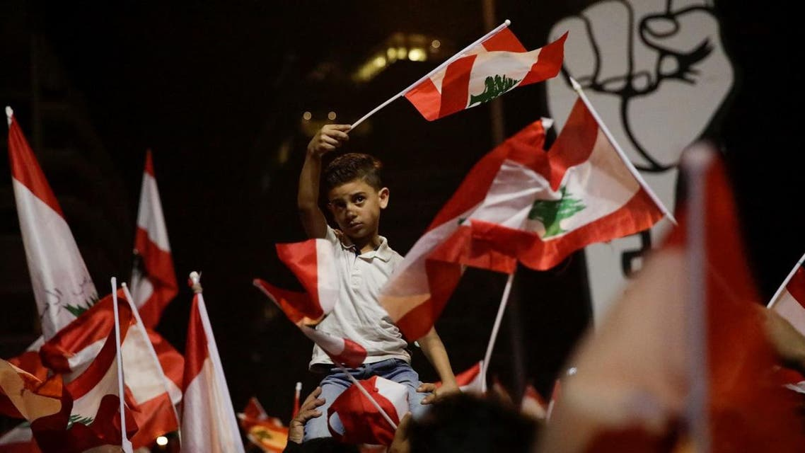 A boy waves a flag as he attends a demonstration at Martyrs' Square during ongoing anti-government protests in Beirut. (Reuters)