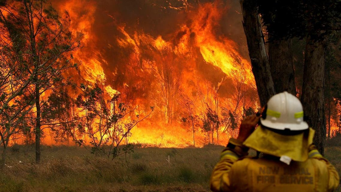 A firefighter on property protection watches the progress of bushfires in Old Bar, New South Wales, Australia November 9, 2019. (Reuters)