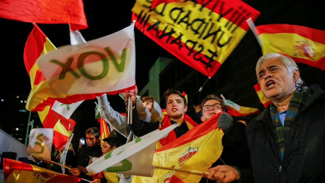 Supporters of Spain's far-right party VOX react as they hold flags during Spain's general election, outside the party headquarters in Madrid. (Reuters)