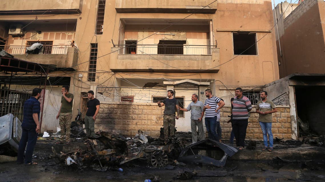 People gather after a car bomb exploded in the town of Qamishli, Syria, Friday, Oct. 11, 2019.  (AP)