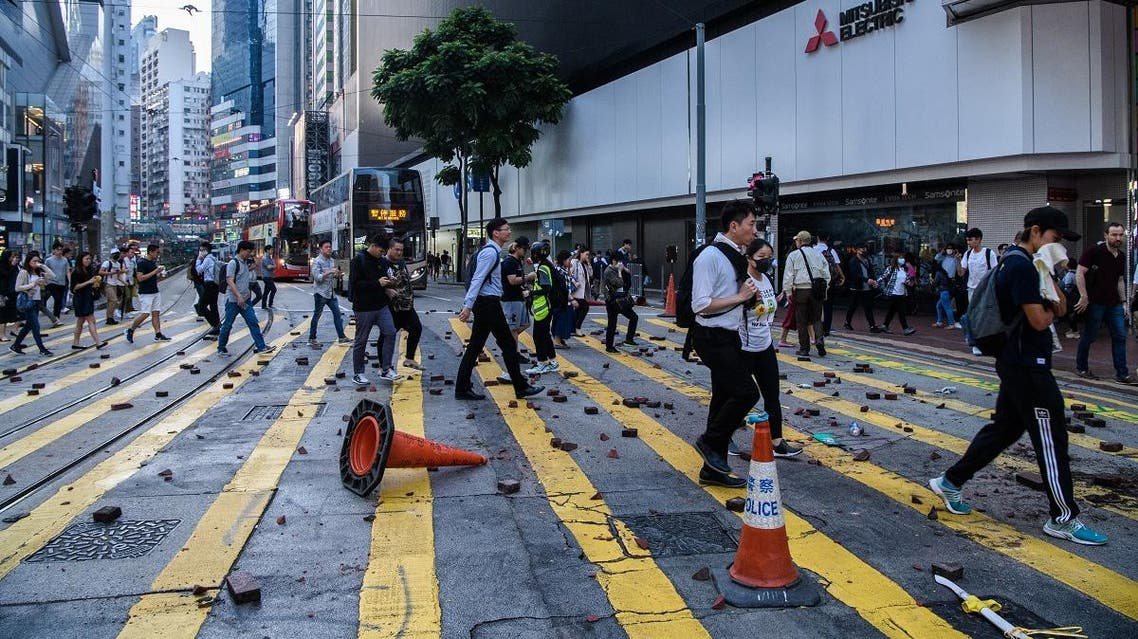 People cross a road after protesters threw bricks onto it in order to stop traffic passing in the Causeway Bay area of Hong Kong on November 11, 2019. (AFP)