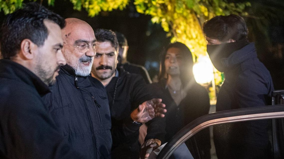 Journalist and writer Ahmet Altan (C) walks with Turkish police as his daughter Senem Altan (R) tries to say him goodbye as he is detained on November 12, 2019. (AFP)