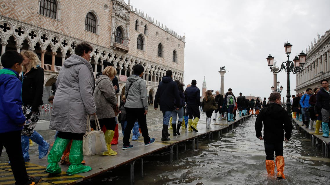 Tourists walk on wooden platforms in flooded St. Mark's Square in Venice, Italy, Thursday, Nov. 1, 2018 as rainstorms and strong winds have been battering the country. (AP)