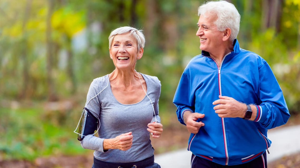 Smiling senior couple jogging in the park stock photo