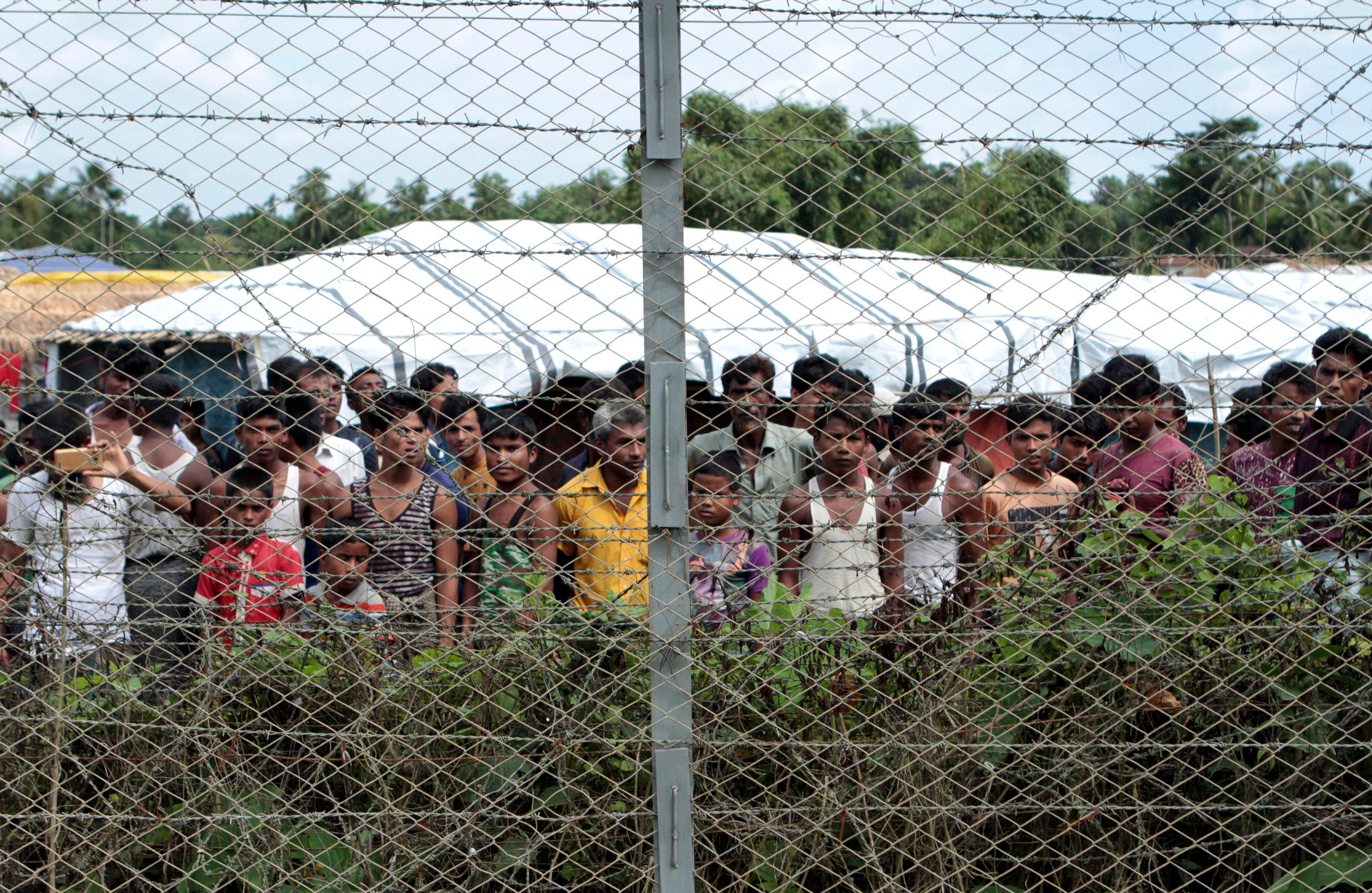 In this June 29, 2018, photo, Rohingya refugees gather near a fence during a government organized media tour, to a no-man's land between Myanmar and Bangladesh, near Taungpyolatyar village, Maung Daw, northern Rakhine State, Myanmar. (AP)