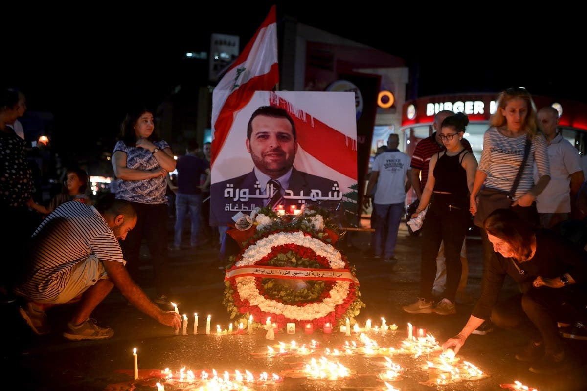 Lebanese demonstrators hold a candle light vigil in the capital Beirut on November 13, 2019, for Alaa Abu Fakhr (photo), killed the day before during ongoing anti-government protests. (AFP)