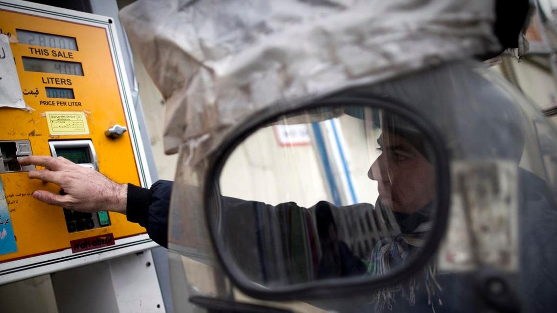 An Iranian man inserts his fuel smart card in the machine to fill his motorcycle at a petrol station in central Tehran. (File photo: AFP)
