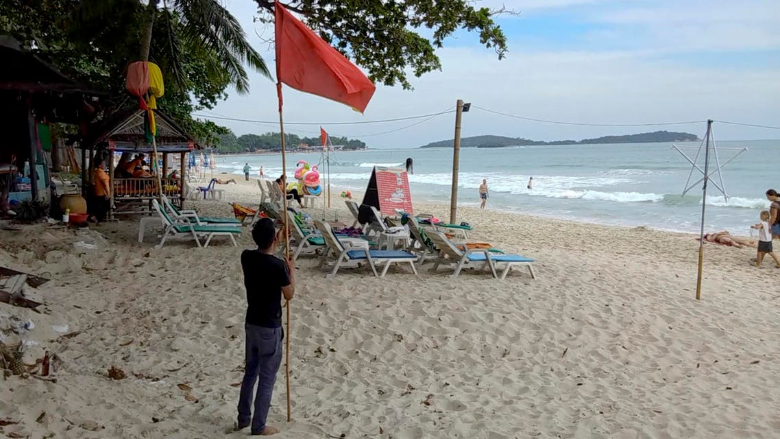 A man raises a red flag indicating rough weather conditions in Chaweng beach, Koh Samui, Thailand, Thursday, Jan. 3, 2019. (AP)
