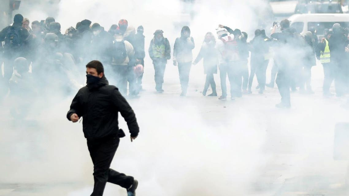 A man runs as protesters stand amidst tear gas fired by police during a demonstration to mark the first anniversary of the yellow vests movement in Paris, France, November 16, 2019. REUTERS