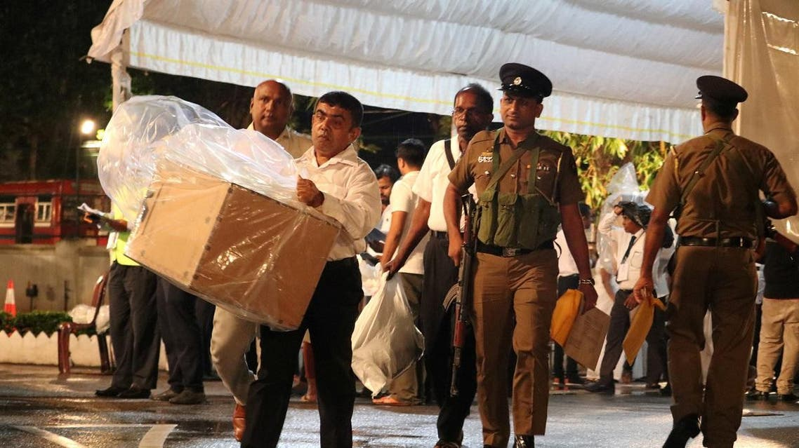 Election officials, assisted by Sri Lankan police officer, arrive with a ballot box to a counting center, after the voting ended during the presidential election day, in Colombo. (Reuters)