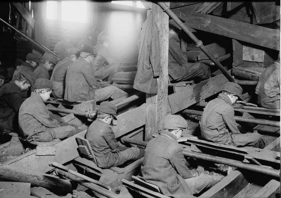 عدد من الأطفال خلال قيامهم بعملية تنقية الفحم