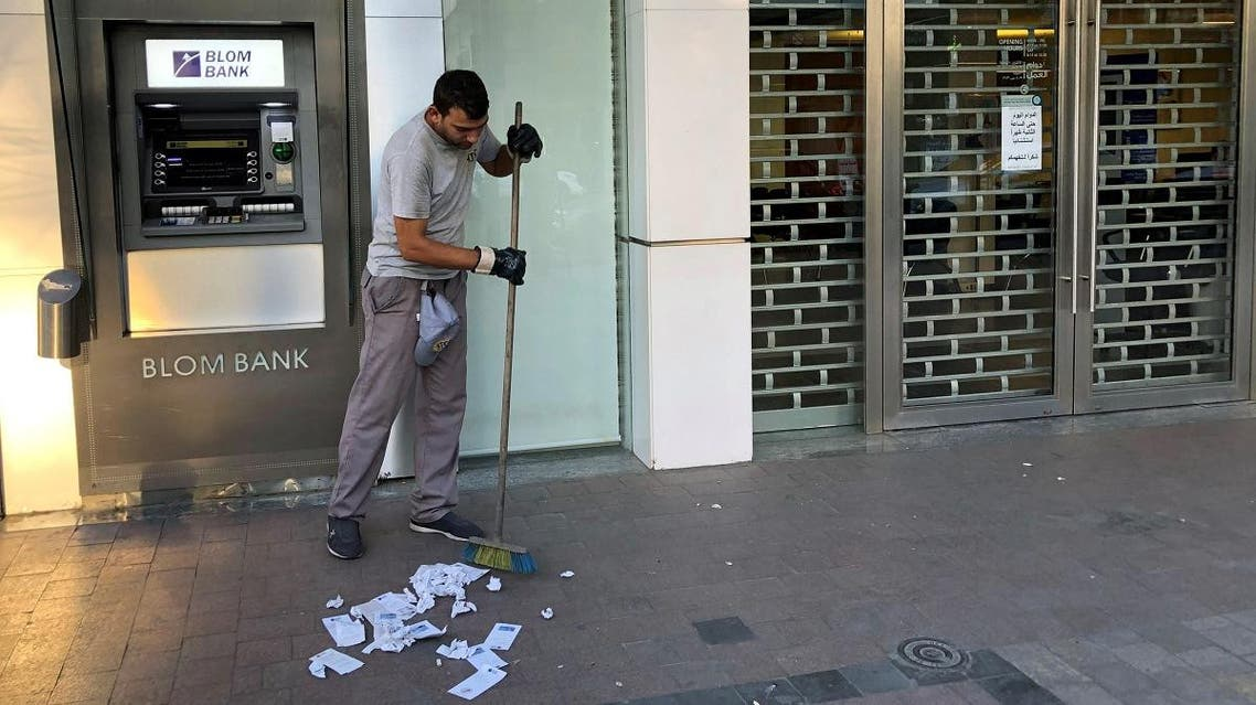 A worker cleans receipts from an ATM machine outside a closed Blom bank branch in the southern city of Sidon. (Reuters)