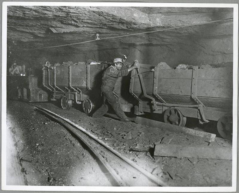 صورة لطفل خلال قيامه بنقل الفحم اعتماداً على عربة قاطرة صغيرة داخل المنجم