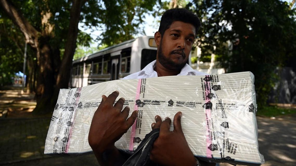 An electoral official waits to board a bus after collecting ballot papers and boxes from a distribution centre for their respective polling stations on the eve of the presidential election, in Colombo. (AFP)