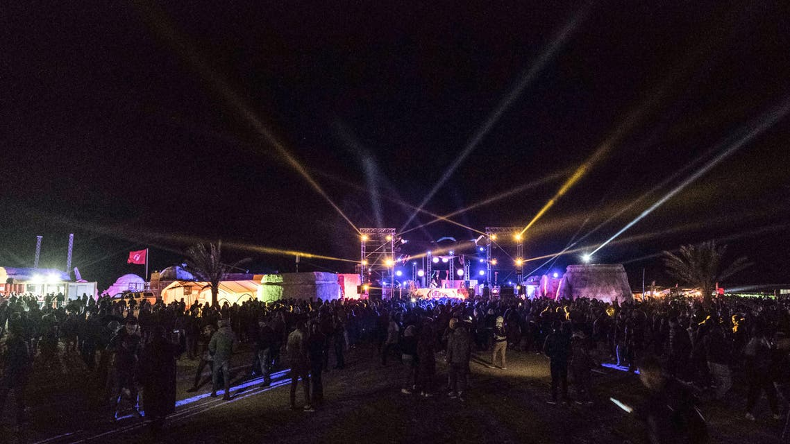"""People dance at the electronic music festival """"Les Dunes Electroniques"""" at Ong Jmel, near the town of Nefta in western Tunisia on November 16, 2019, where the original Star Wars film was shot. (AFP)"""