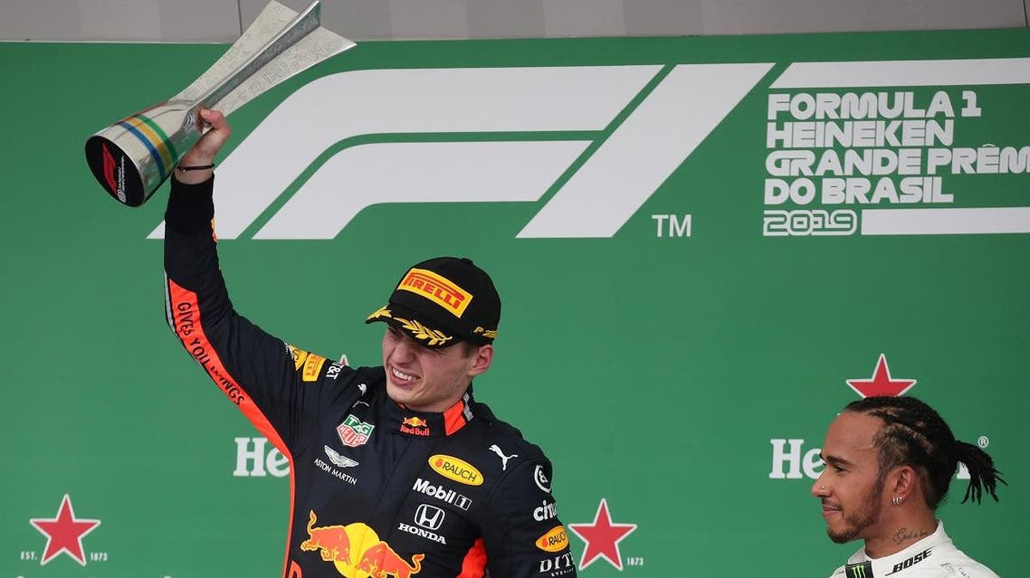 Brazilian Formula One Grand Prix winner Red Bull's Max Verstappen celebrates on the podium as third placed Mercedes' Lewis Hamilton looks on. (Reuters)