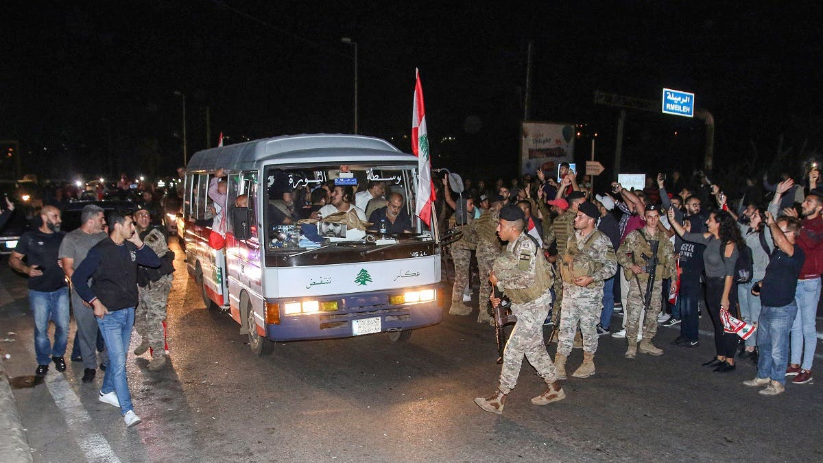 "Lebanese anti-government protesters arrive in a ""revolution"" bus escorted by Lebanese army soldiers in the southern city of Sidon on November 16, 2019. (AFP)"