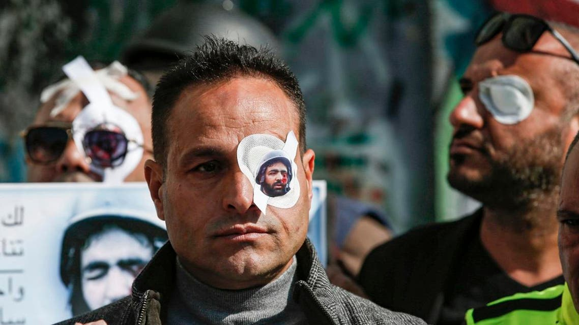 A Palestinian journalist wears a paper eye patch during a demonstration by Israel's controversial separation barrier in Bethlehem in the occupied West Bank on November 17, 2019, in solidarity with Palestinian cameraman Muath Amarneh. (AFP)