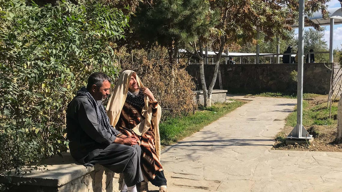 A woman and a man sit on a bench in a park that is being upgraded with wider footpaths, more lights and seating areas as part of a program to make public spaces safer and more accessible for women in Kabul, Afghanistan. (Thomson Reuters Foundation)