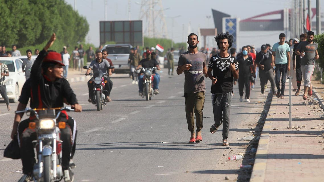 Iraq's um qasr port- protesters run away during clashes with security officers (Reuters)